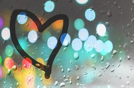 Heart on the window. Painted with a finger on misted glass during rain. Bright bokeh from a street lamp. Standard-Bild - 147822113