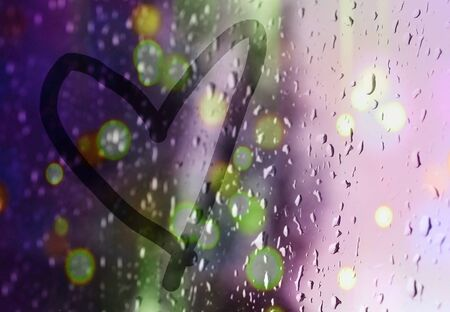 Heart on the window. Painted with a finger on misted glass during rain. Bright bokeh from a street lamp. Standard-Bild