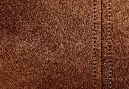 The texture of genuine leather. Brown background.