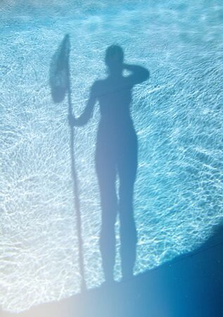 Silhouette of a girl with a butterfly net. Cleaning the dirty empty pool of algae, water stone and limescale. The beginning of the bathing season in the hot summer.