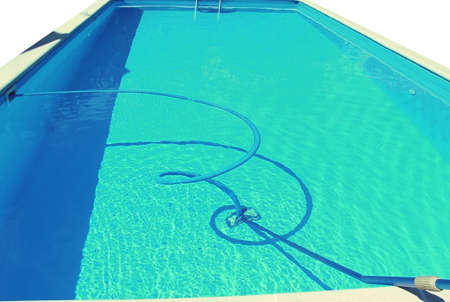 Cleaning a dirty empty pool from algae, water stone and limescale with a special pump. The beginning of the swimming season is hot summer. Standard-Bild