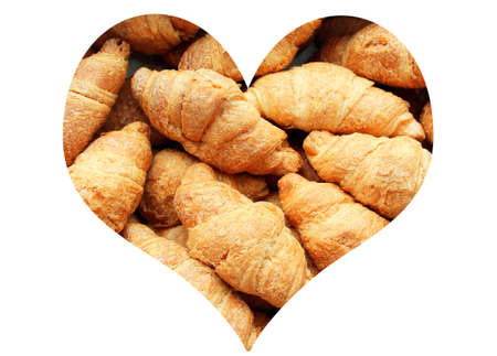 Croissants with condensed milk in the shape of a heart isolated on a white background.