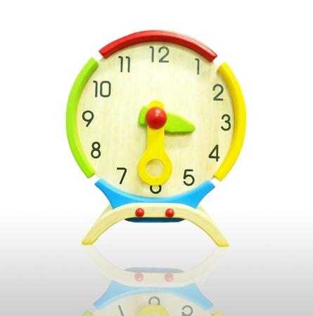 zeitarbeit: Bunte h�lzerne Uhr auf einem wei�en Hintergrund Lizenzfreie Bilder