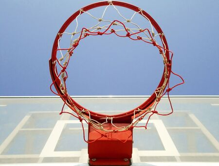 A basketball hoop, net and backboard on a playground, shot from below.                             photo