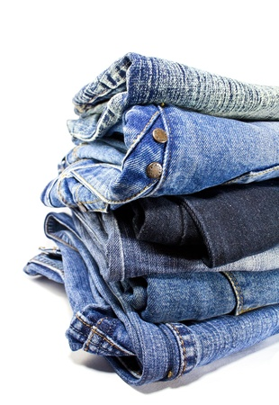 stack of blue denim jeans on white background photo