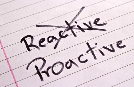 reactive: Crossing out reactive and writing proactive  Stock Photo
