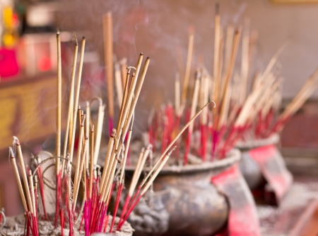 Burning incense sticks at a buddhist temple in thailand photo