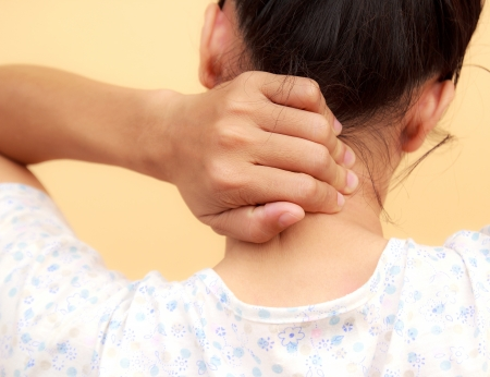 woman back pain: Woman holds a hand on pain neck