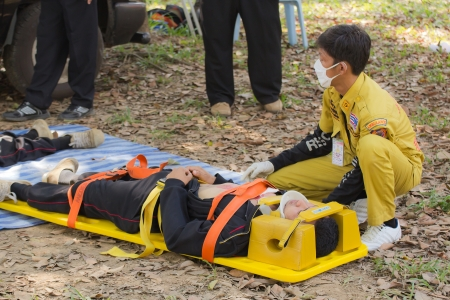 l hand: PHRAE,THAILAND - DECEMBER 20 : Unidentified  men are first aid training from staff  the hospital on  December 20, 2012 at local parks, Muang, Phrae, Thailand. Editorial