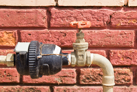Rusting old water valve with water meter photo