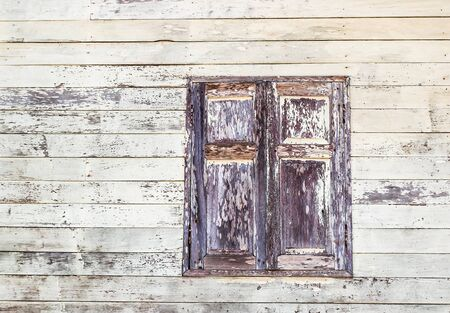 ramshackle: The window of the old wooden log house on the background of wooden walls Stock Photo