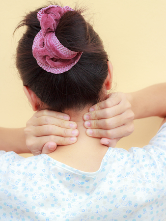 Woman holds a hand on neck  pain, isolated photo