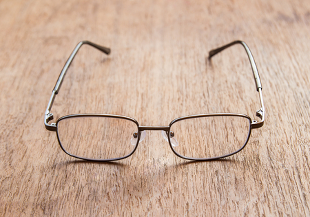 visually: Reading Glasses on a wooden floor. Shallow depth of field