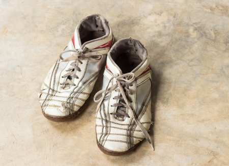 Dirty old shoes on marble floor