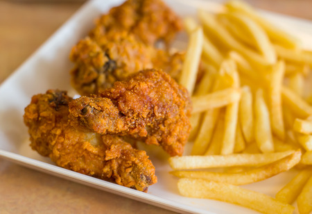 spicy fried chicken with french fries in white plate