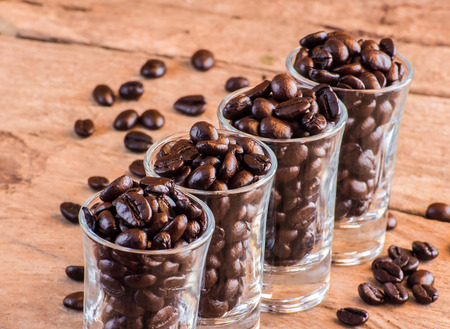 Coffee beans in a glass on wooden photo