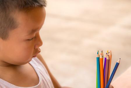 Closeup portrait of a little boy look at colorful pencils