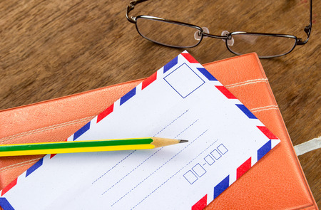 old envelope: White vintage envelope, pencils, notebook and glasses on a wood floor