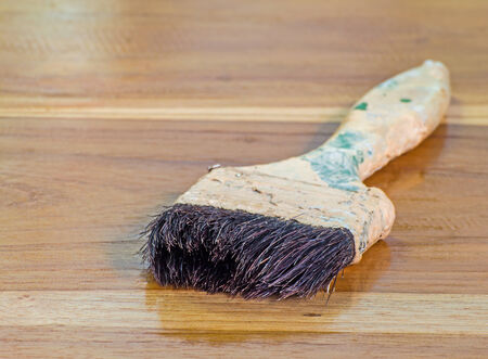 old wood floor: Old paint brush laying on wooden floor