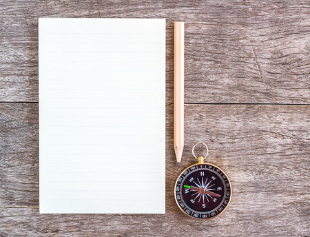 Open blank notebook with pencil and compass over a wooden background. Top View. photo
