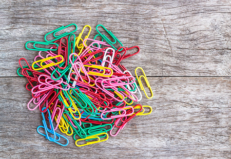 Colorful paperclips on wood background photo