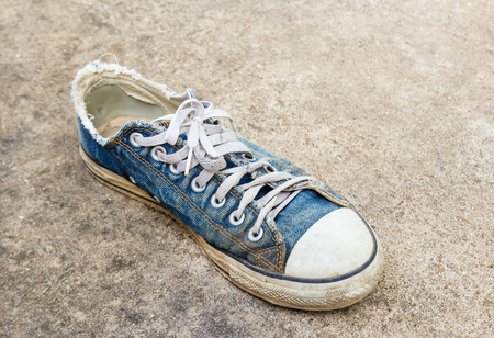 Dirty old shoes on the floor Stock Photo
