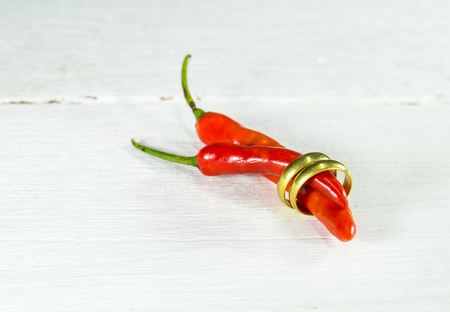 gold textured background: Gold Ring and Hot Chili Peppers on wood textured background
