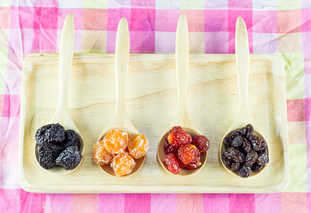 Close up dried fruit in wooden spoon on wooden plate Imagens