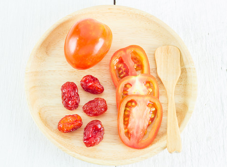 domates: Fresh tomato and dried tomatoes in wooden plate on white table Stock Photo