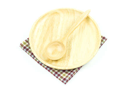 Wooden spoon in wooden plate on a tablecloth on white background photo