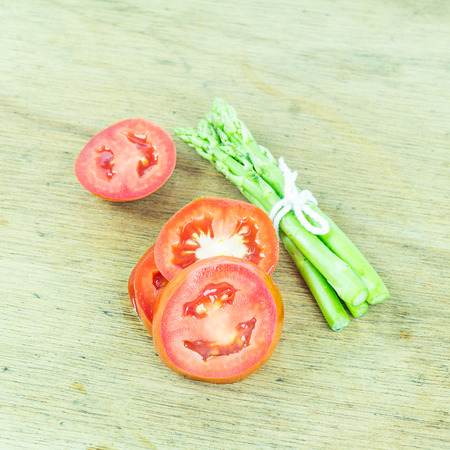 slice tomato: Close up green asparagus and slice tomato on wood background Stock Photo