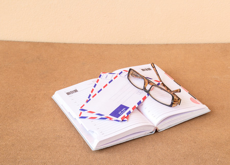 Notebook, glasses and envelope on wood background photo