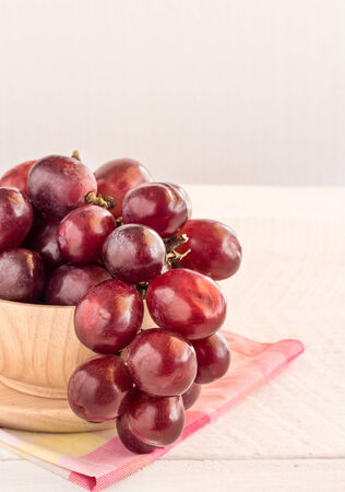 Red grapes in wooden bowl on a wooden table background photo