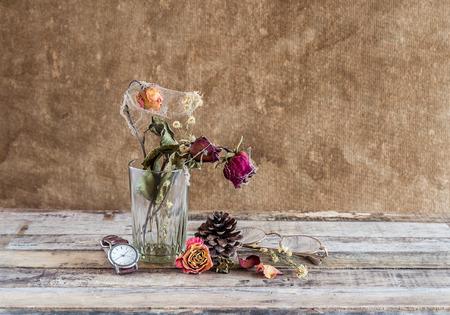 Todavía fotografía de la vida: Rosa marchita en vidrio y ver en el fondo de madera Foto de archivo - 35857249