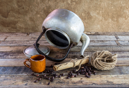 paper roll: Still life photography :Old kettle,paper roll,rope reel and coffee beans on wooden background