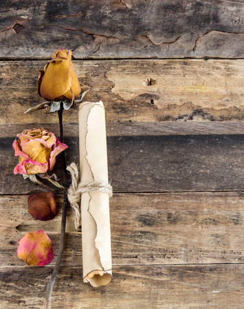 writ: Old paper roll and dry rose on wooden background Stock Photo