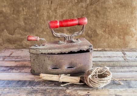drudgery: Retro still life with old rusty iron ,paper roll and rope reel on wooden table Stock Photo