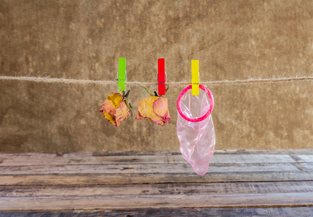 Red condom and dry rose hanging on line on wooden background