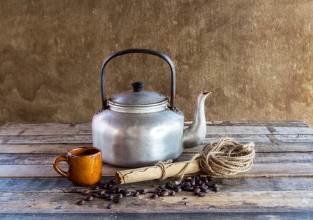 Still life photography :Old kettle,paper roll,rope reel and coffee beans on wooden background