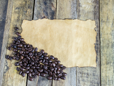 Old paper and coffee beans on wooden table background Stock Photo
