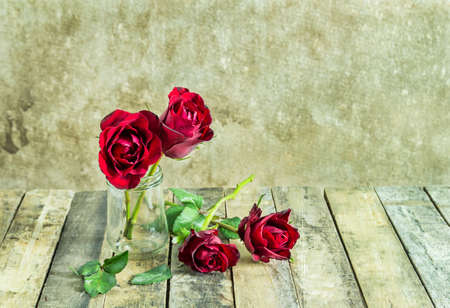 red roses: Fresh red rose in glass bottle on wooden background