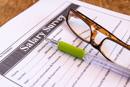 Glasses and pen on salary survey from on the table photo