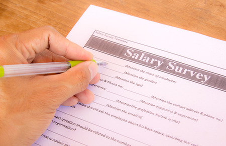 Hand with pen choosing salary survey from on the table photo