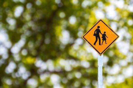Yellow traffic sign on green blurred bokeh background photo