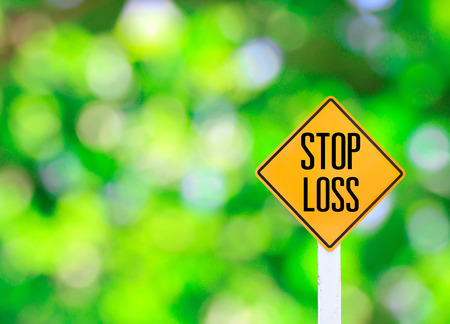 Yellow traffic sign text for stop loss and green bokeh blur background