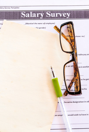Glasses and pen on salary survey from on the table
