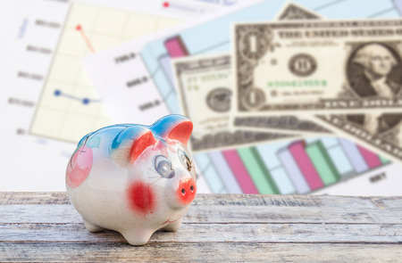 holiday profits: Piggy bank on wooden table over dollars and financial paper graphs background. saving money concept. Stock Photo