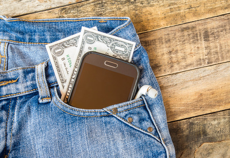 Dollar money and smart phone in pocket blue jeans on wooden background 免版税图像