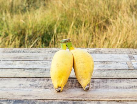 朝の日差しの屋外木製テーブルの上熟したバナナ