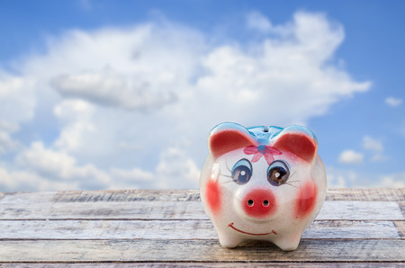 Piggy bank on wooden table over blurred blue sky background. saving money concept. photo
